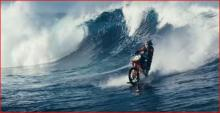 Motorcycle riding a wave