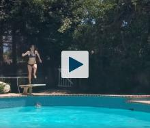 Woman jumping from diving board