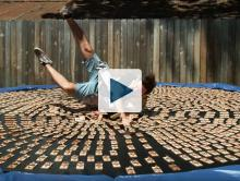 Dan jumping onto a trampoline covered in mousetraps