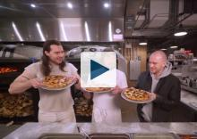 Three men holding pizzas