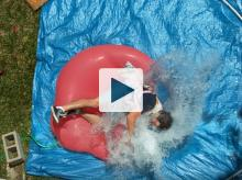 Dan falling onto giant water balloon