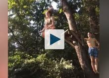 Woman jumping from platform with rope swing
